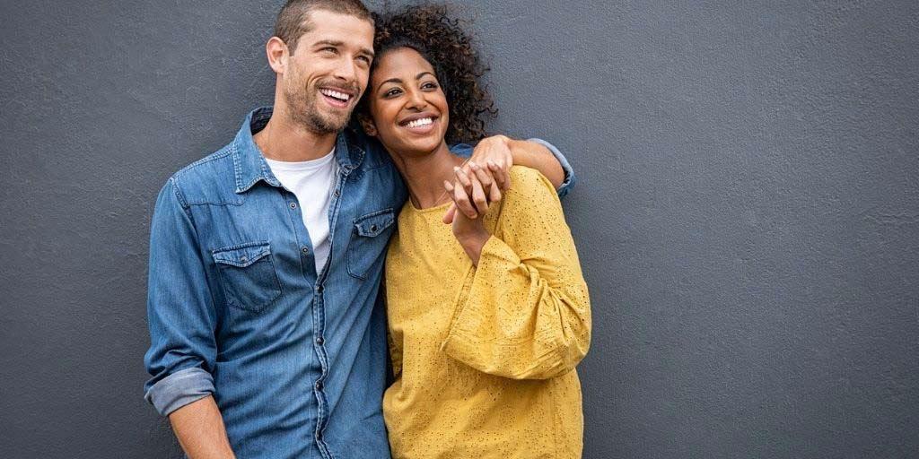 A young biracial couple embrace while flashing big smiles