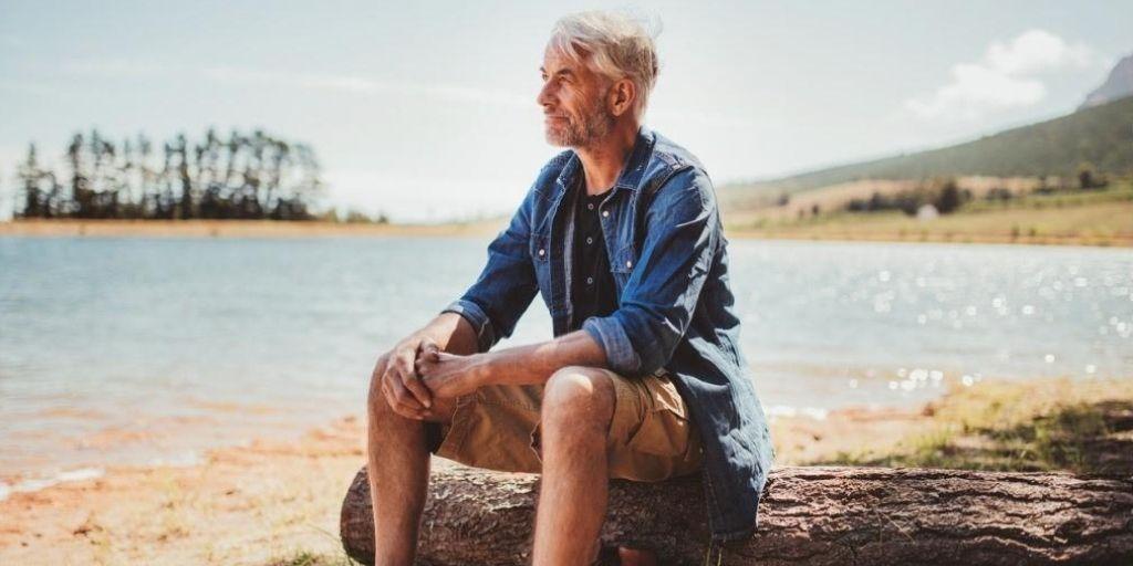 An older white man enjoys his retirement on the beach.